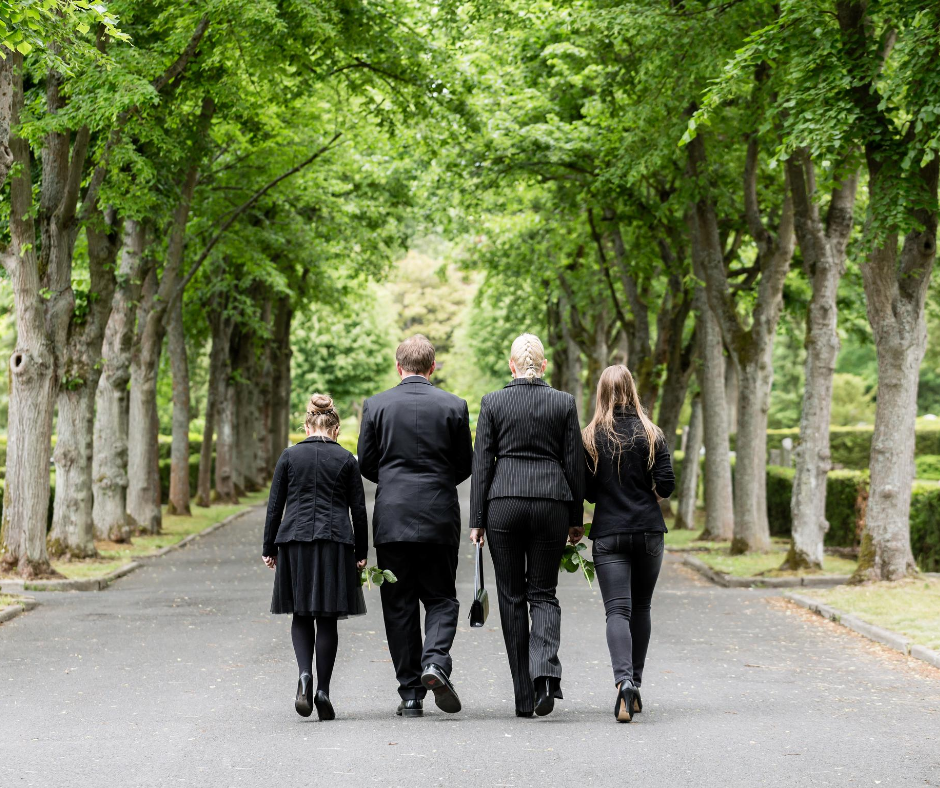 photo of 4 adults in black walking down a tree-lined path after a funeral | Overnight Caskets | Buying a Casket Online